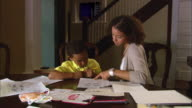 MS, PAN, mother helping son (6-7) do homework at dining table, Westfield, New Jersey, USA