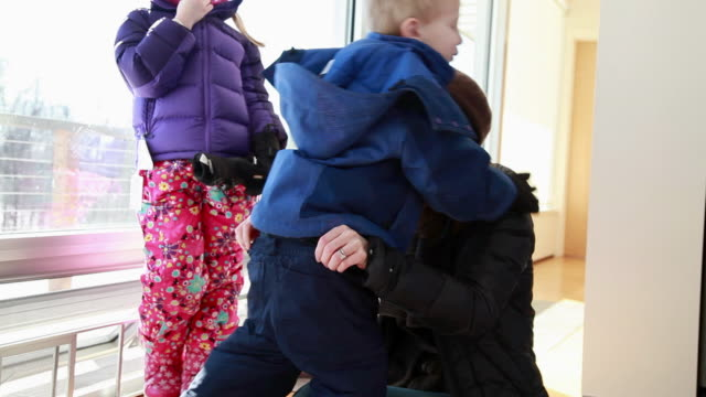 Mother helping son get dressed into winter clothing
