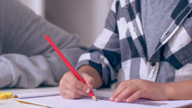 Mother helping son to draw lines with ruler in copybook