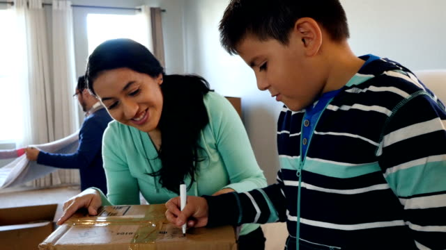 Mother helping young son label cardboard box while packing to move to new home