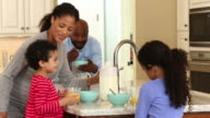 Mother helps two daughters make breakfast in kitchen/ Richmond, Virginia USA