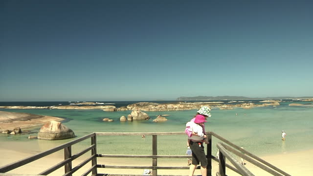WS Mother holding baby daughter walking down stairs on beach / Denmark, Western Australia, Australia