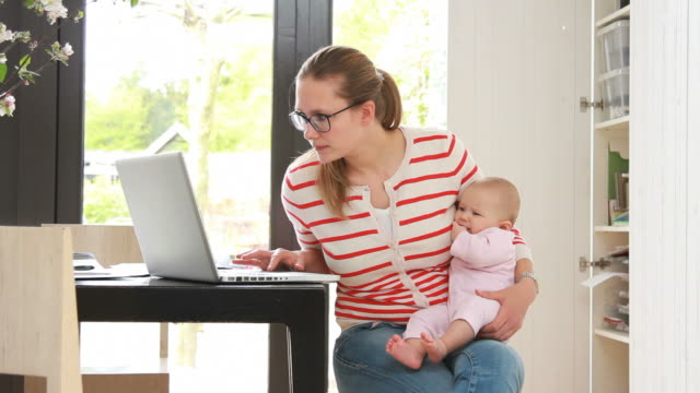 Mother holding baby working from home on phone
