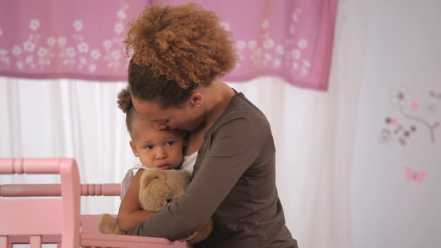 MS PAN Mother hugging daughter (2-3) in crib / Richmond, Virginia, USA