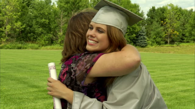 MS Mother hugging daughter wearing graduation gown and holding diploma / Appleton, Wisconsin, USA