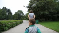 Mother is pulling cart with her son
