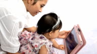 Mother is showing a cartoon to her baby with tablet