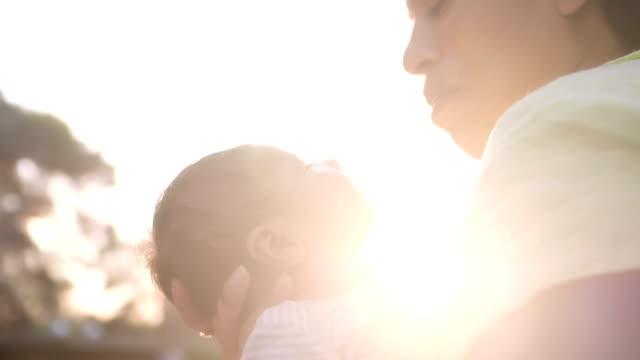 Mutter küsst Baby auf Wange