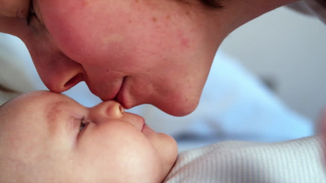 CU Mother leaning face to face over baby daughter (2-5 months) in bed, Brussels, Belgium
