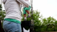 Mother lifts toddler daughter from swing on playground and sets her on ground