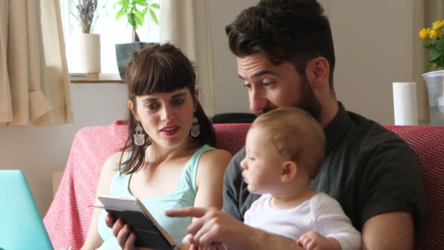 Mother looks up from work to engage with father reading story to baby son.