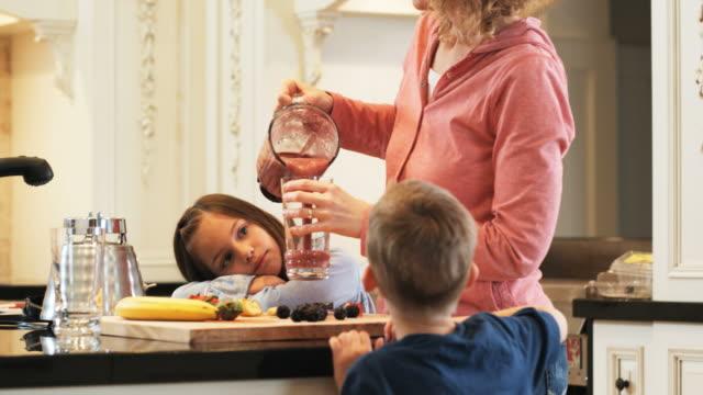 mother making a fruit smoothie in a blender for her children