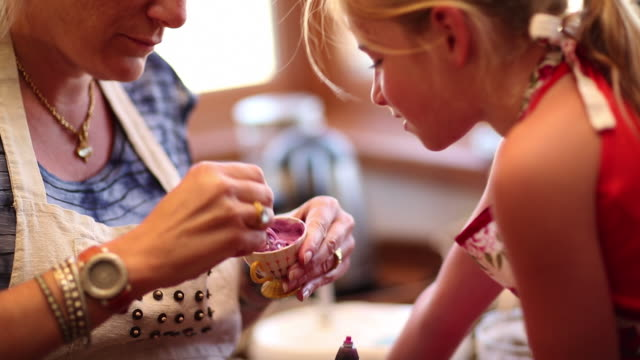 MS Mother making cream in small cup in kitchen with her daughter / Lamy, New Mexico, United States