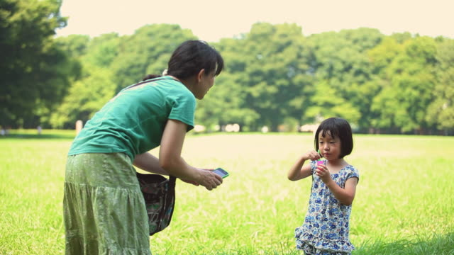 MS Mother photographing daughter (4-5) blowing bubbles in park / Koganei, Tokyo, Japan