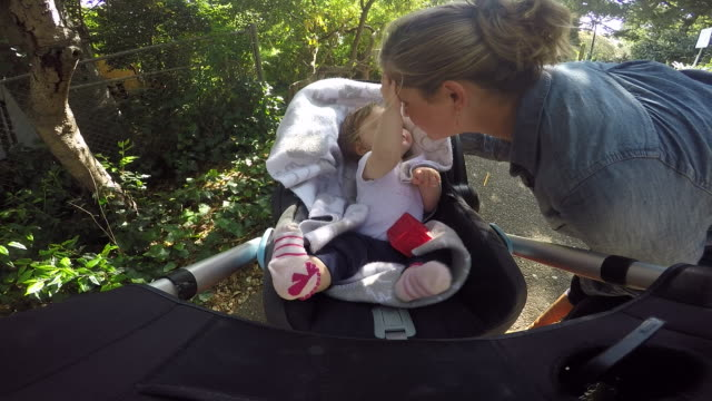 A mother picking up her daughter from a stroller outside in a park.