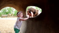 Mother playing peekaboo with toddler daughter at outdoor park and playground