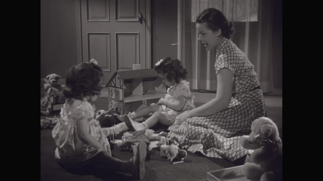 MS Mother playing with her twin daughters and a doll house in living room / United States