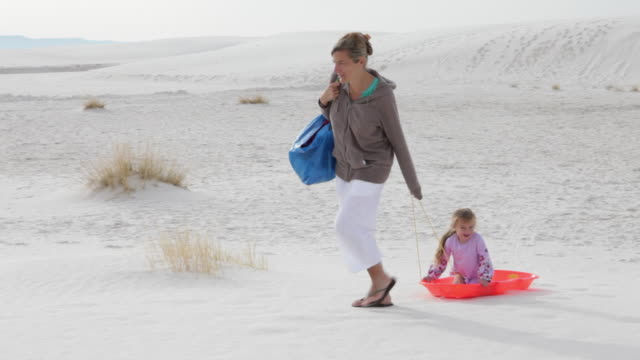 WS PAN Mother pulling daughter (2-3) on sled in white sands / White Sands, New Mexico, USA