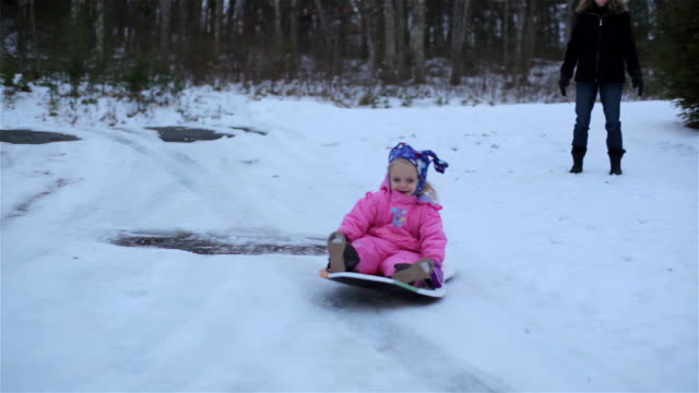 Mother pushes young girl down hill on snow sled