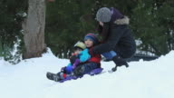 WS TS Mother pushing children (2-7) on sledge downhill in snow, girl (10-11) in background / Richmond, Virginia, USA