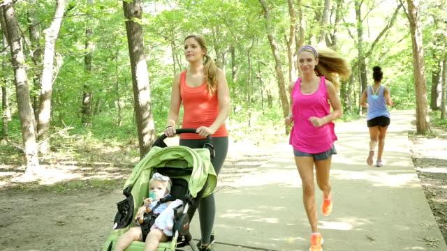 Madre spingendo primi passi nel Passeggino a tre ruote durante l'esercizio nel parco