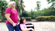 Mother pushing young daughter in wheelchair outdoors