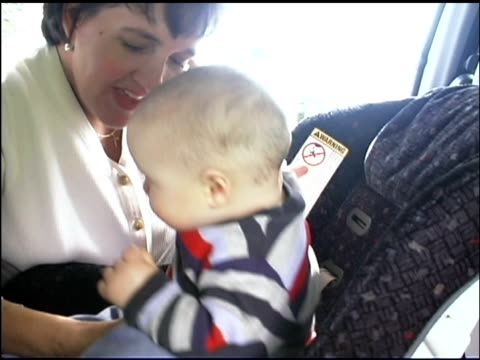 Mother putting baby into safety seat in car