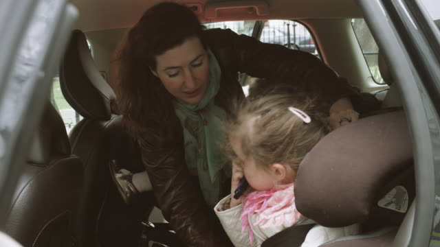 Mother putting child in safety belt in car