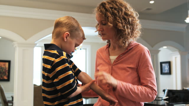 mother putting Neosporin and a bandage on her son's arm