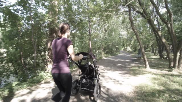 Moeder actief wandelen met baby wandelwagen in Park