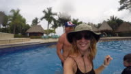 Mother selfie dances as father throws son around in a pool at a resort.