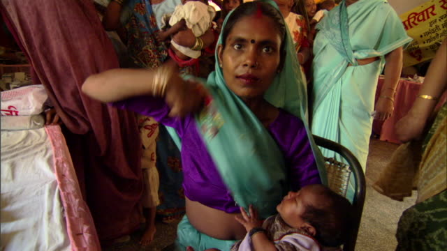 MS PAN Mother settling into chair with baby at SIFPSA health clinic, Agra, Uttar Pradesh, India