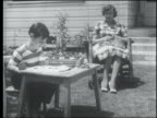B/W 1952 mother sits knitting while son finger paints outdoors
