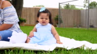 MS Mother sitting with infant daughter on blanket in backyard