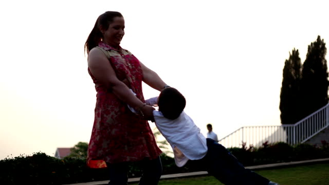 Mother spinning her son in the nature