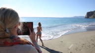Mother takes digital tablet pic of daughter running into sea
