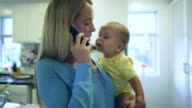 TS MS Mother talking on the phone while holding her baby.
