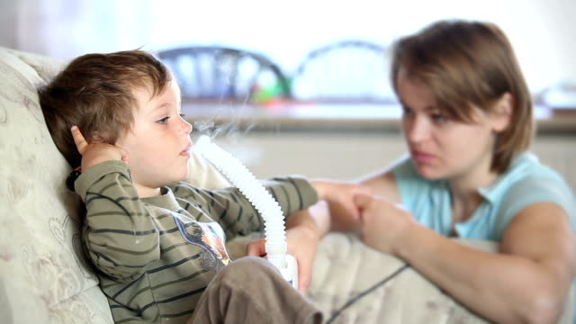A mother talks to her son as he uses a nebulizer.