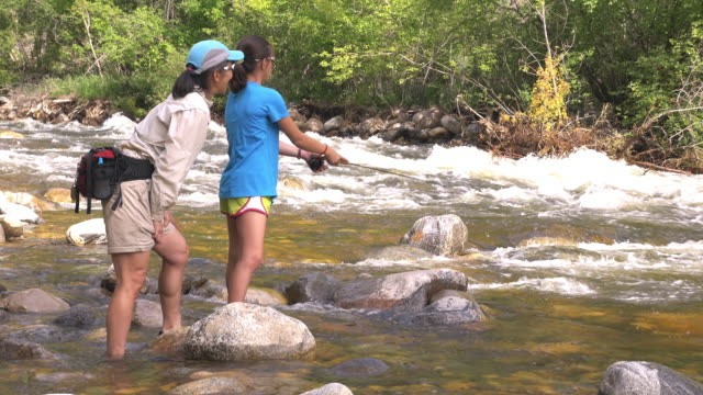 Mother teaching daughter fly fishing in river