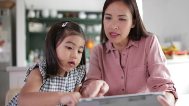 Mother teaching Daughter how to use digital tablet