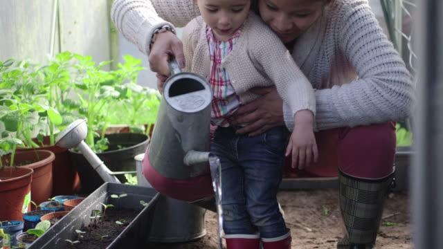 Mother teaching girl planting