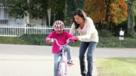 MS PAN ZOTU Mother teaching young daughter how to ride bicycle / Richmond, Virginia, United States