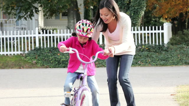 MS TU Mother teaching young daughter how to ride bicycle / Richmond, Virginia, United States