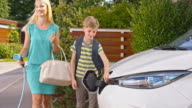 SLO MO Mother unplugging electric car and son closing lid