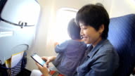 HD : Mother using Smart Phone on airplane
