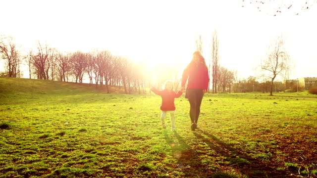 Mother walking with cute disabled child in park at sunset
