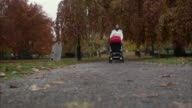 Mother walking with perambulator Sweden.