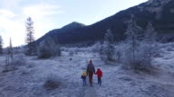 Mother walking with their kids in a frozen landscape