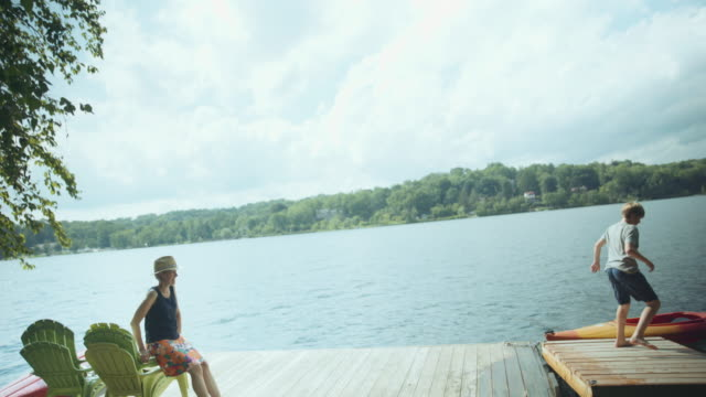 Mother watching Caucasian boy jumping on floating dock at river