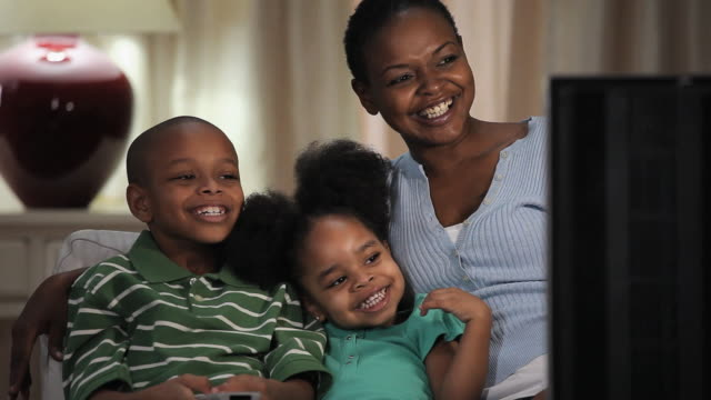 MS Mother watching television with daughter (2-3) and son (8-9) / Richmond, Virginia, USA